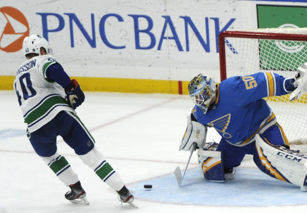 St. Louis Blues goalie Jordan Binnington (50) blocks a shot in a shootout by Vancouver Canucks' Elias Pettersson (40), of Sweden, in an NHL hockey gam