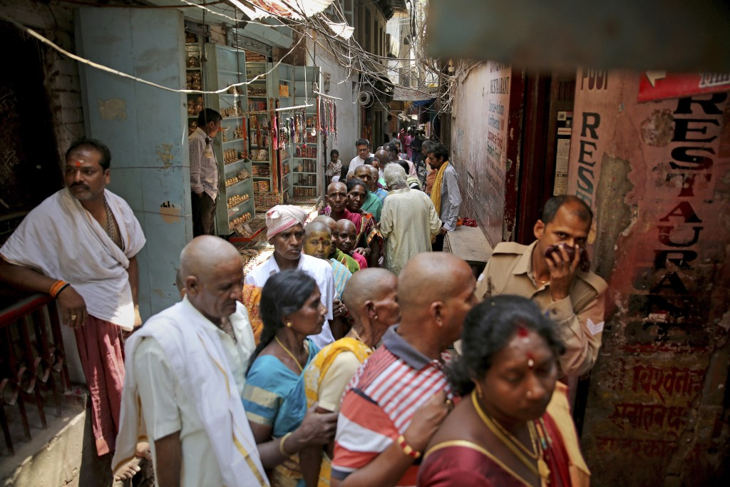 In this March 22, 2019, photo, Hindu devotees stand in queue in a narrow lane to enter into Vishwanath temple, in Varanasi, India. In the Indian city