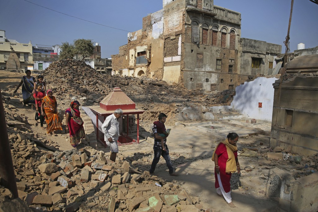 In this March 19, 2019 photo, Hindu devotees walk barefoot through debris of demolished houses to reach river Ganges at the site of a proposed grand p