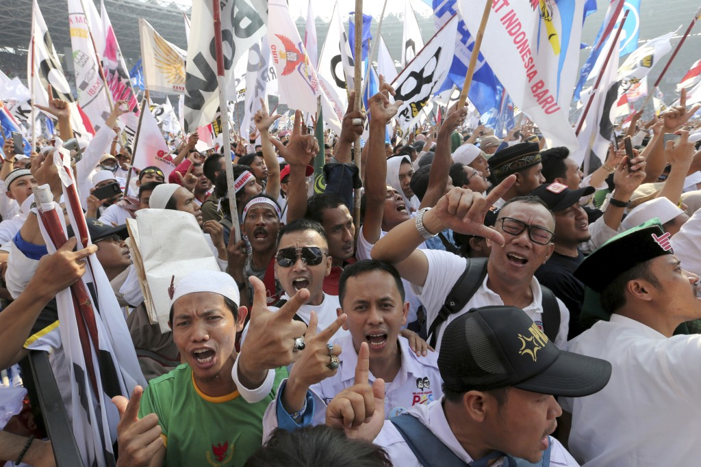 In this Sunday, April 7, 2019, file photo, supporters of Indonesian presidential candidate Prabowo Subianto shout slogans during a campaign rally of h