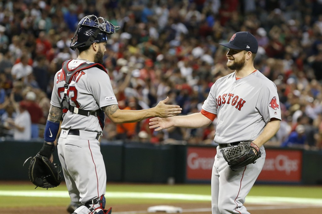 Boston Red Sox pitcher Ryan Brasier and Blake Swihart (23) celebrate after defeating the Arizona Diamondbacks 1-0 during a baseball game, Sunday, Apri