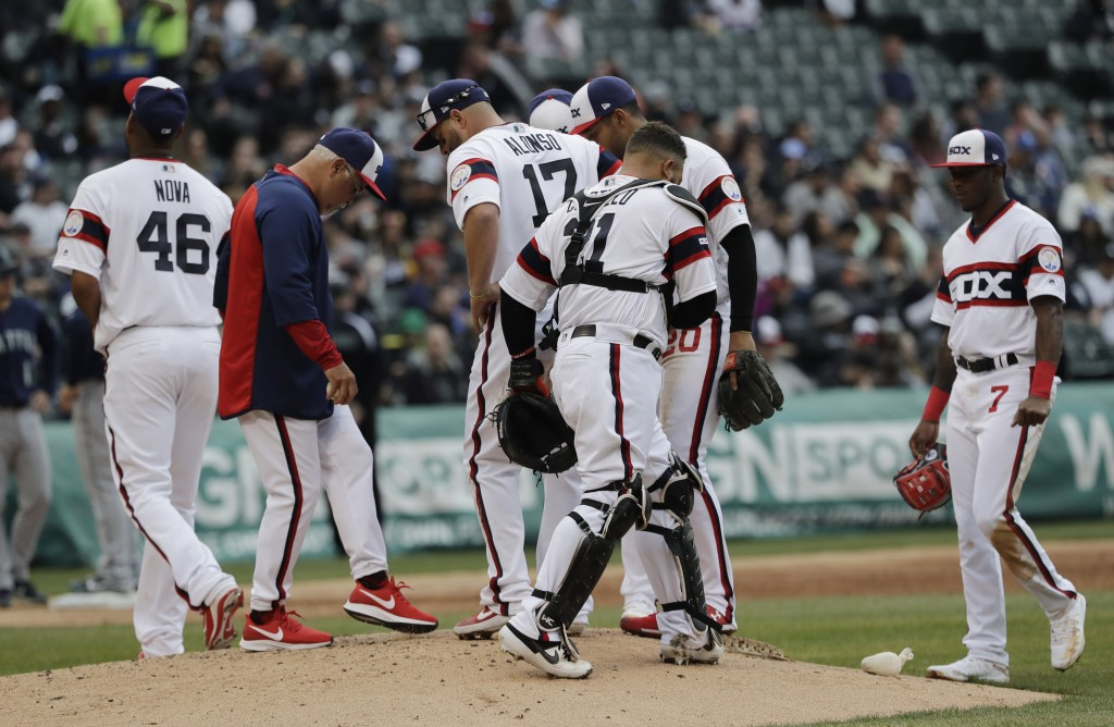 Chicago White Sox manager Rick Renteria, second from left, talks with his team as he waits for relief pitcher Ryan Burr during the third inning of a b...