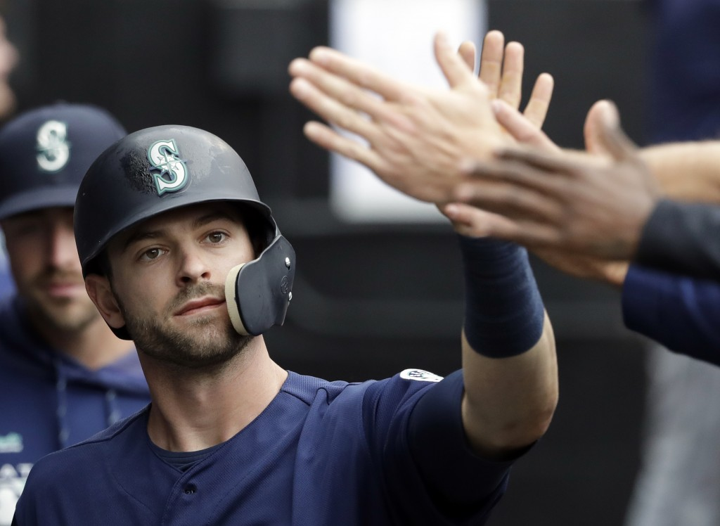 Seattle Mariners' Mitch Haniger celebrates with teammates after scoring on a one-run single by Edwin Encarnacion during the third inning of a baseball...