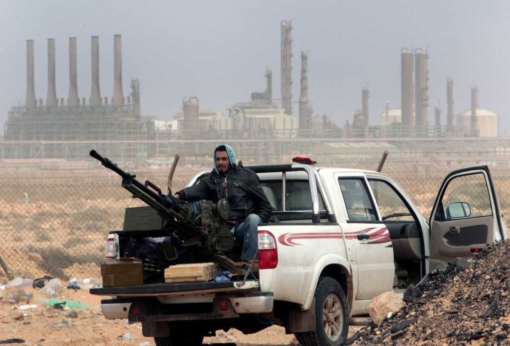 FILE - In this March 5, 2011 file photo, an anti-government rebel sits with an anti-aircraft weapon in front an oil refinery in Ras Lanouf, eastern Li
