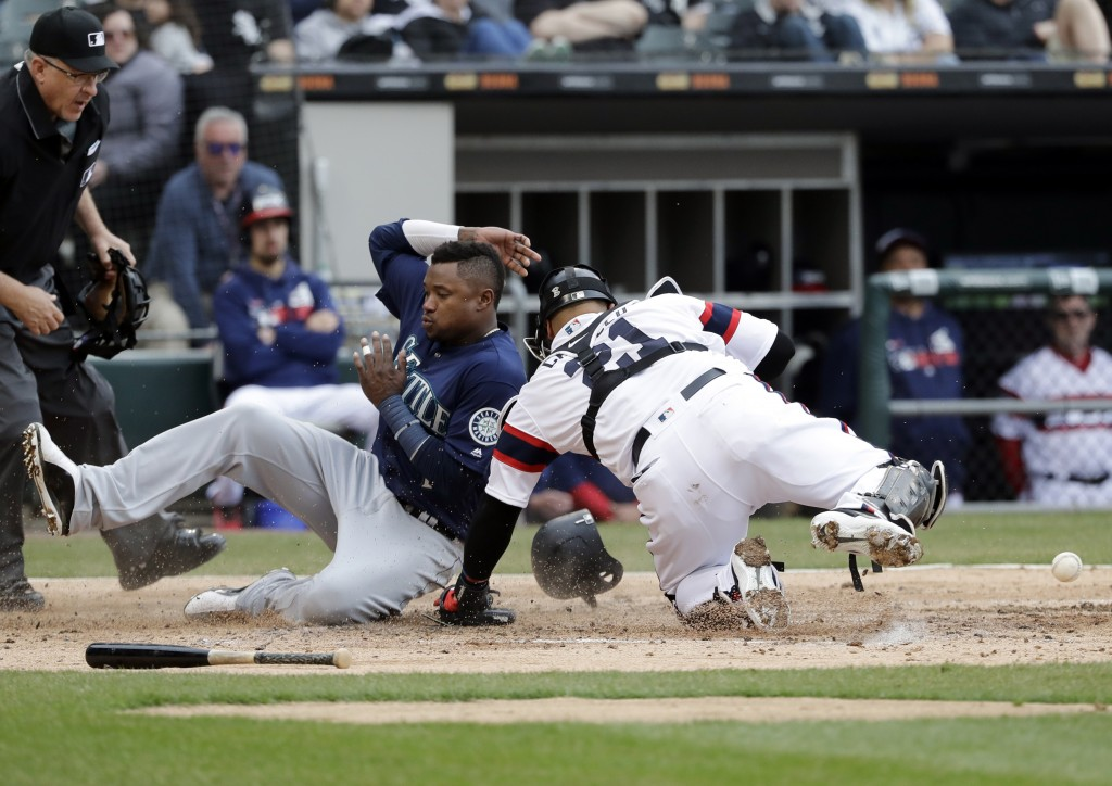Seattle Mariners' Tim Beckham, left, scores on a three-run double by Daniel Vogelbach as Chicago White Sox catcher Welington Castillo missed the ball ...