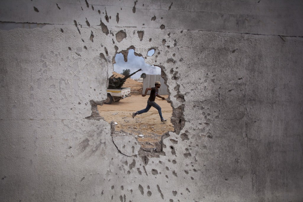 FILE - In this Oct. 7, 2011, file, photo, a Libyan revolutionary fighter runs for cover while attacking pro-Gadhafi forces in Sirte, Libya. Libya has