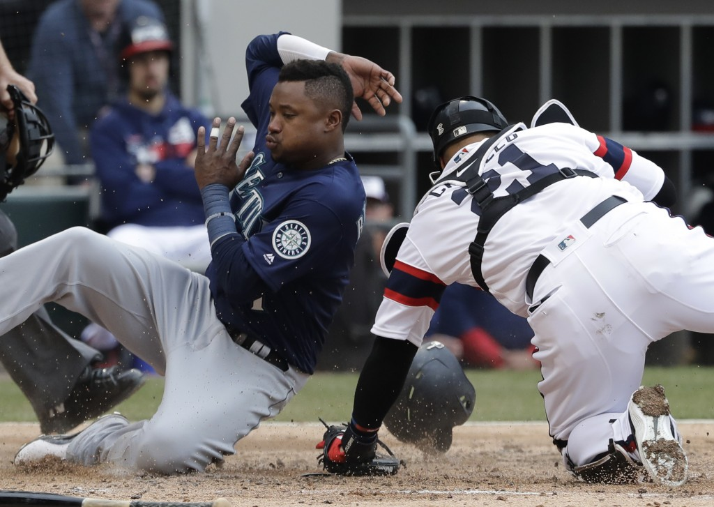 Seattle Mariners' Tim Beckham, left, scores on a three-run double by Daniel Vogelbach as Chicago White Sox catcher Welington Castillo misses the ball ...