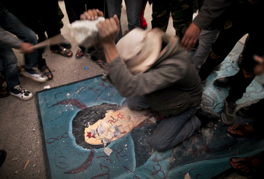 FILE - In this Feb. 26, 2011, file photo, a Libyan man uses a stone to hit a defaced billboard of Libyan leader Moammar Gadhafi during a demonstration