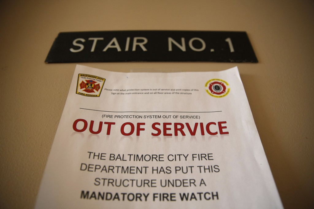 In this Feb. 22, 2019 photo, a sign alerts residents in Rosemont Tower in Baltimore that the fire sprinkler system is out of service, requiring a fire...