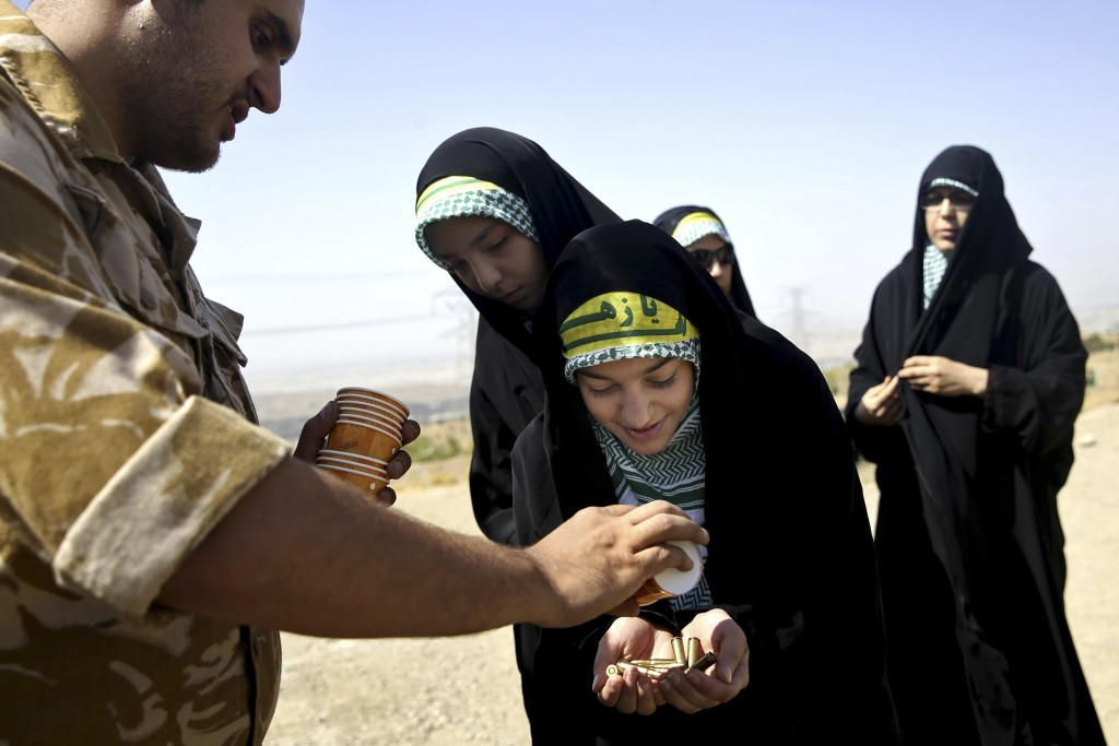 FILE-- In this Aug. 22, 2013 file photo, a female member of the Iranian Basij paramilitary militia, affiliated to the Revolutionary Guard, receives bu...