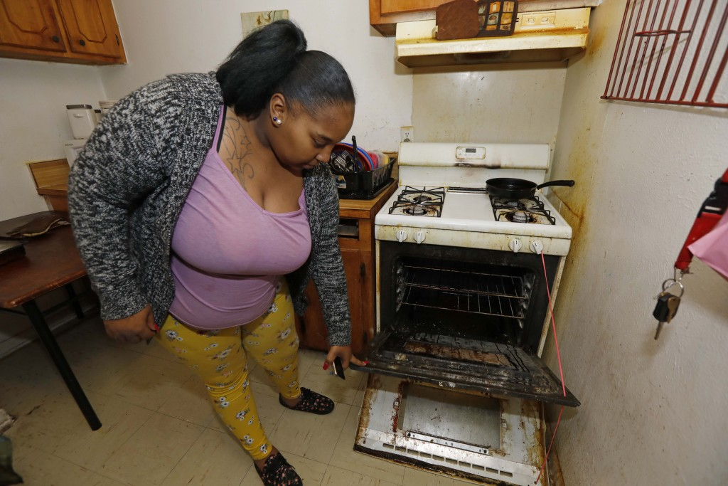 In this Feb. 20, 2019 photo, Destiny Johnson shows the broken door to her oven that she uses string to hold together, in her apartment in Cedarhurst H...