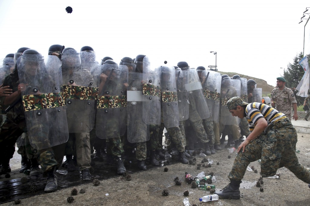 FILE - In this April 24, 2015 file photo, members of the Iranian paramilitary Basij force, affiliated to the Revolutionary Guard, re-enact a riot situ...