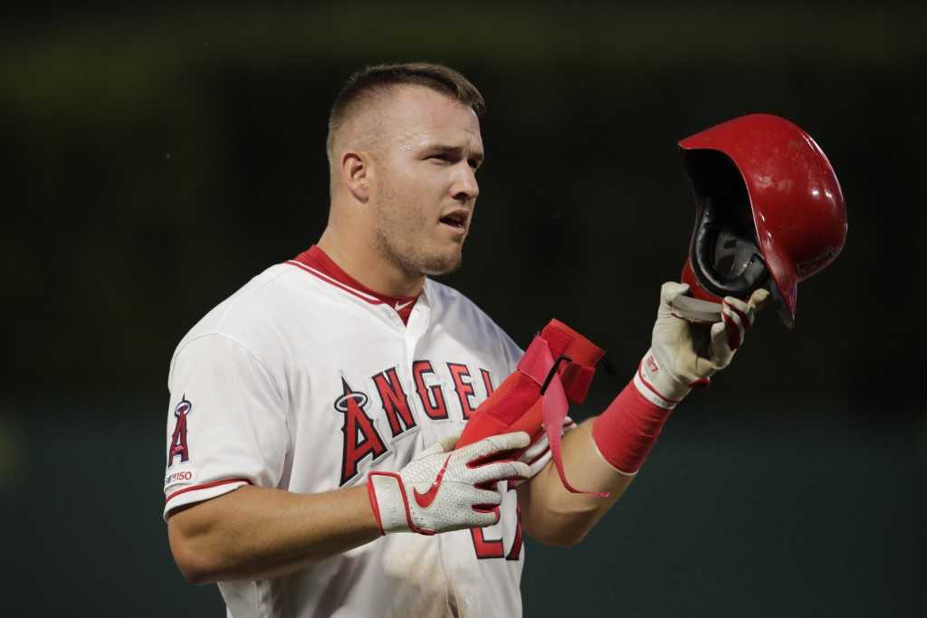 Los Angeles Angels' Mike Trout takes off his helmet after the first inning of a baseball game against the Milwaukee Brewers, Monday, April 8, 2019, in