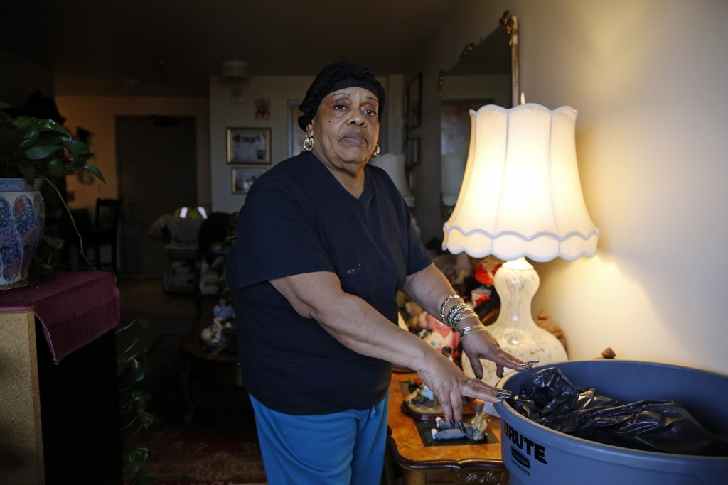 In this Feb. 26, 2019 photo, Della Thomas stands with a trash can that she says management provided to catch water dripping from her ceiling during ra...