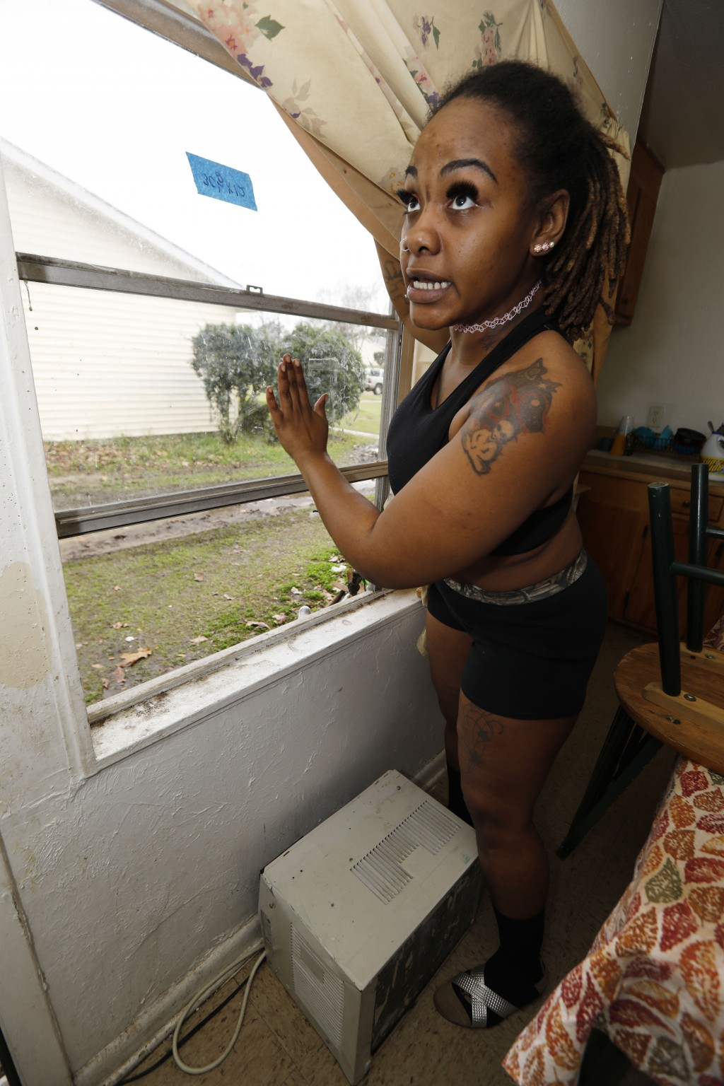 In this Feb. 20, 2019 photo, Whitley Williams demonstrates how a recently repaired window does not open easily, preventing her from using a window air...