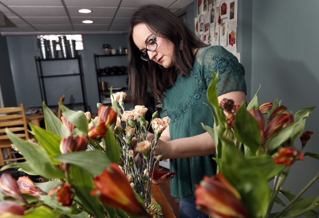 In this April 1, 2019, photo Liz Mally, who owns LPF Blooms, works on a centerpiece in her studio in her basement in Ferndale, Mich. Mally learned the