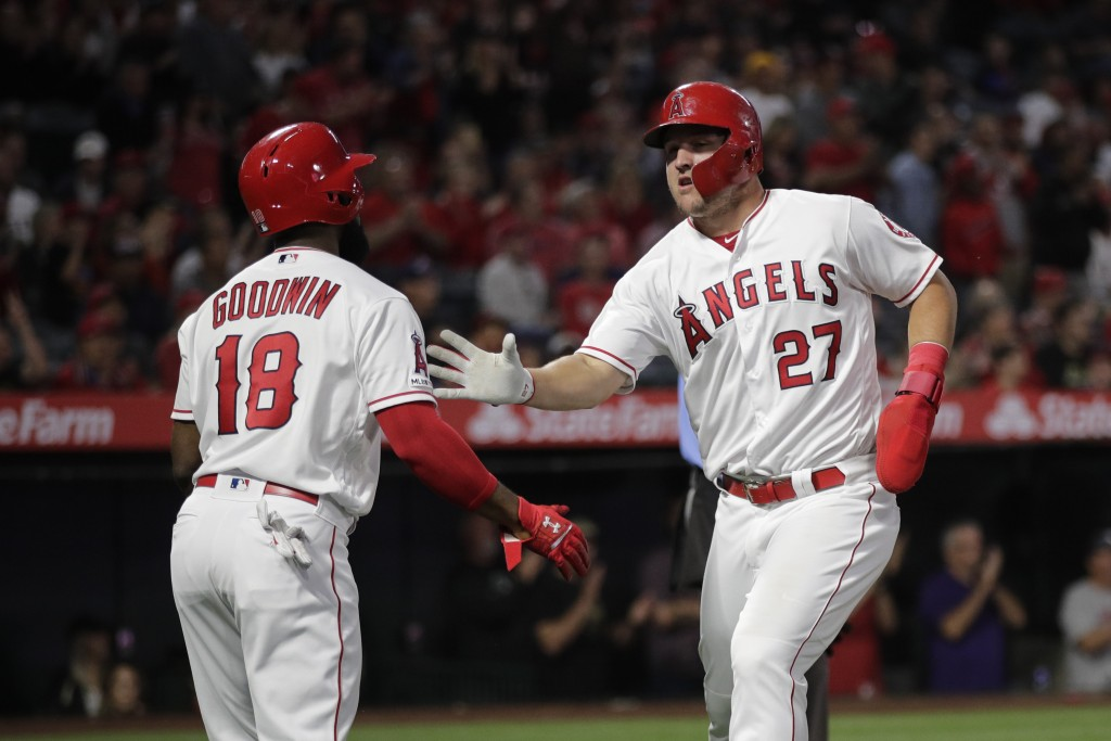 Los Angeles Angels' Mike Trout, right, is greeted by Brian Goodwin after he scored on a single by Albert Pujols during the first inning of a baseball