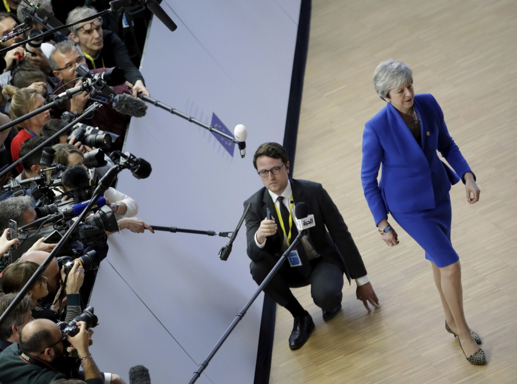 British Prime Minister Theresa May, right, walks away after speaking with the media after she arrives for an EU summit at the Europa building in Bruss...