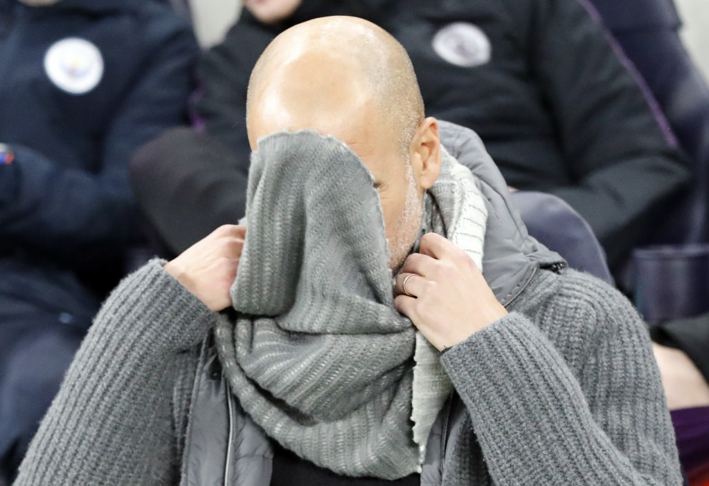 Manchester City coach Pep Guardiola fixes his sweater during the Champions League, round of 8, first-leg soccer match between Tottenham Hotspur and Ma