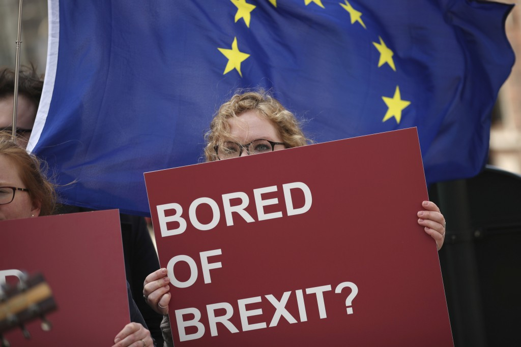 An anti-Brexit campaigner holds a sign in front of an EU flag during a protest outside EU headquarters in Brussels, Wednesday, April 10, 2019. Europea...