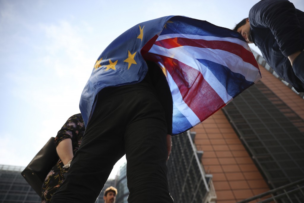 An anti-Brexit campaigner wears an EU and Union Flag during a protest outside EU headquarters in Brussels, Wednesday, April 10, 2019. European Union l...