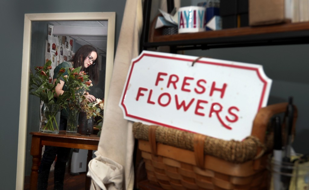 In this April 1, 2019, photo Liz Mally, who owns LPF Blooms, is reflected in a mirror as she works on a centerpiece in her studio in her basement in F...