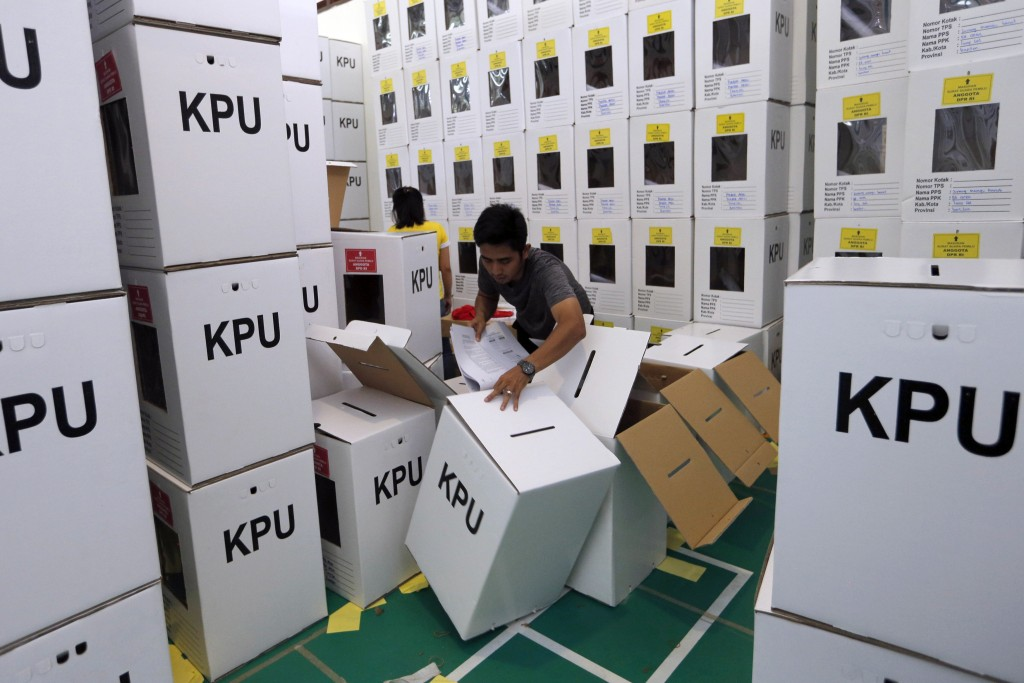 In this Wednesday, April 10, 2019, file photo, an Indonesian electoral worker prepares ballot in the boxes to be distributed to polling stations in Ja