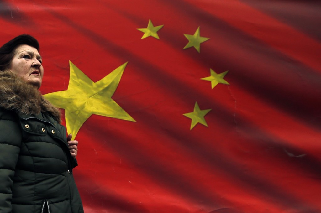 In this photo taken Friday, March 1, 2019, a woman walks by Chinese flag placed on a street in Belgrade, Serbia. Chinese investments have been booming
