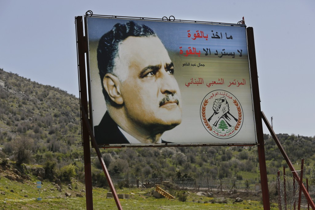 In this Tuesday, April 9, 2019 photo, a giant poster that shows the late Egyptian leader Gamal Abdul-Nasser, near the barbed wire that separates Leban