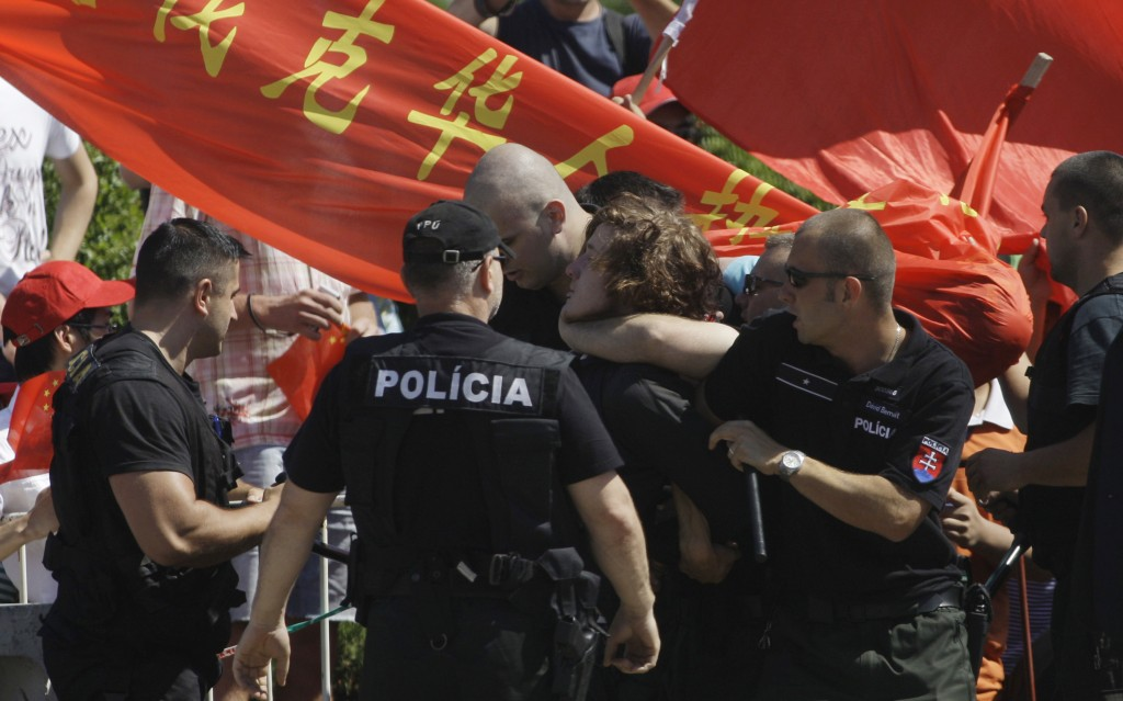 FILE - In this June 18, 2009, file photo, police arrests a human rights activist protesting against the Chinese government prior to the visit of Chine