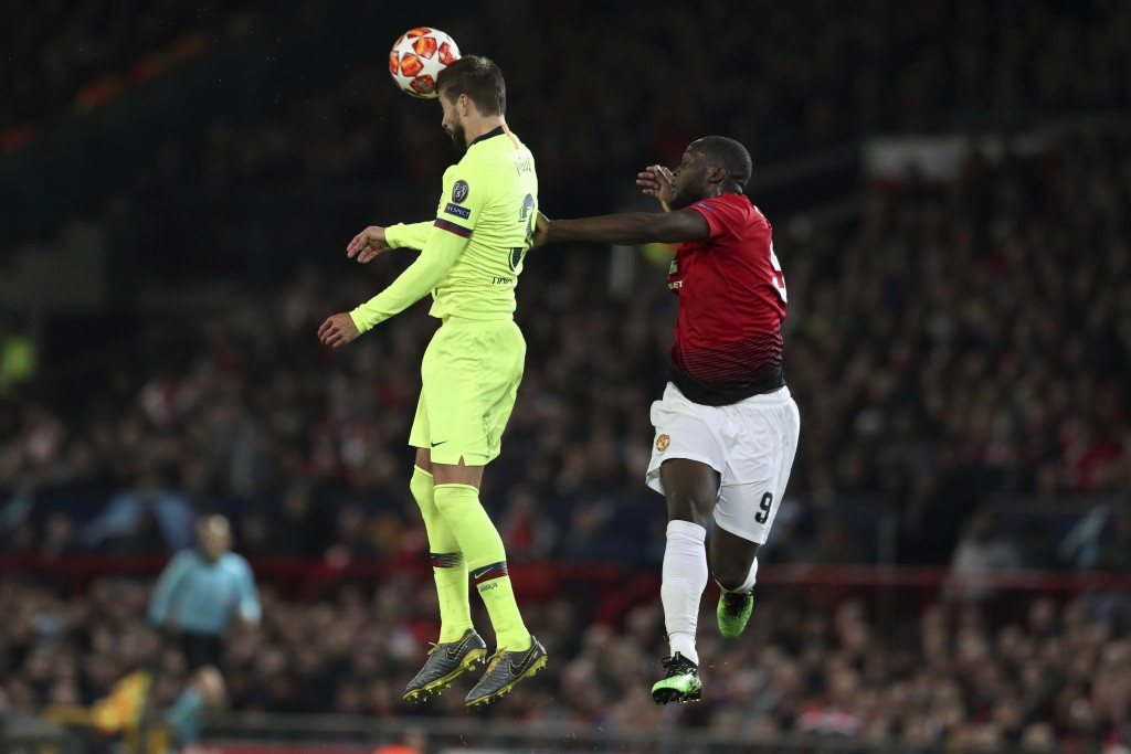 Barcelona's Gerard Pique, left, and Manchester United's Romelu Lukaku jump for the ball during the Champions League quarterfinal, first leg, soccer ma