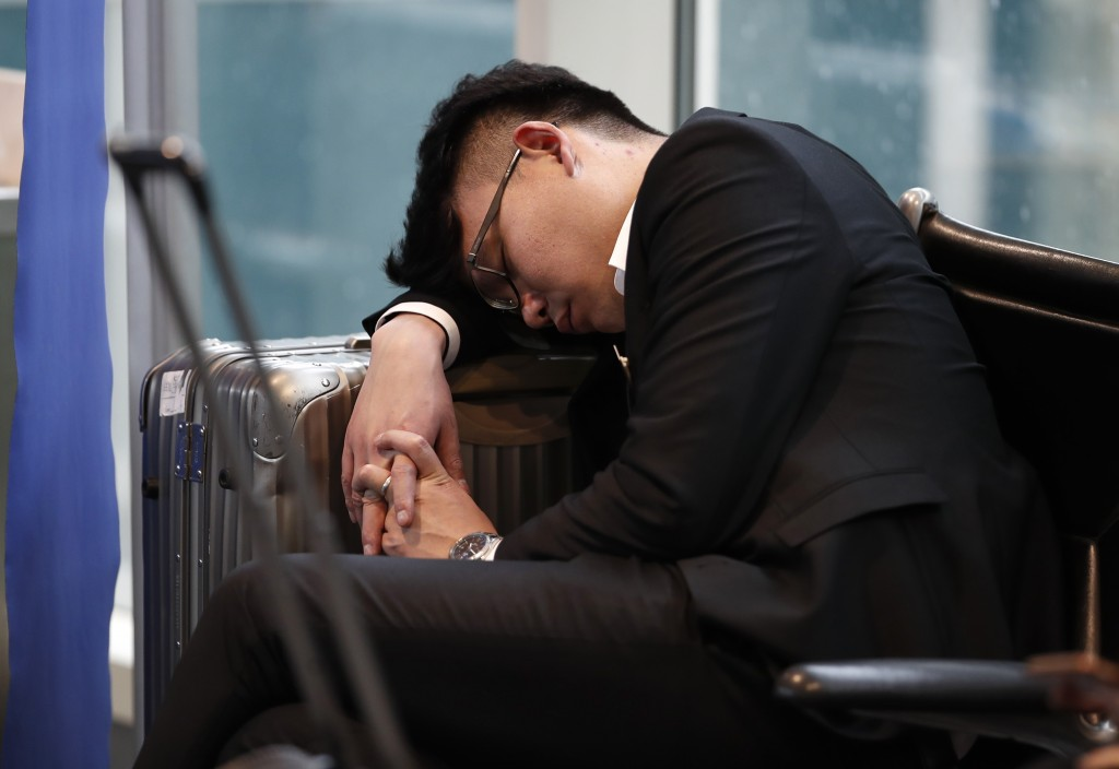 An unidentified man sleeps on his luggage in Denver International Airport Wednesday, April 10, 2019, in Denver. Forecasters are predicting from four t...