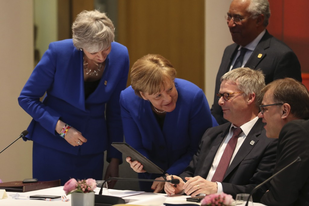 Britain's Prime minister Theresa May, left, and Germany's Chancellor Angela Merkel, center, look at a tablet with other leaders including Portugal's P...