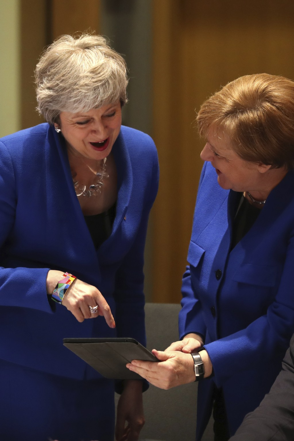 Britain's Prime minister Theresa May, left, and Germany's Chancellor Angela Merkel, right, look at a tablet ahead of a pre-dinner meeting during an EU...