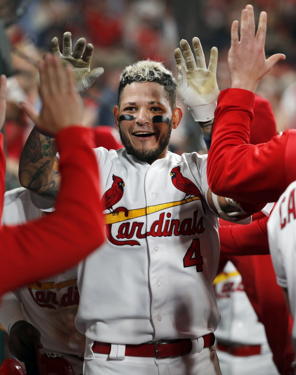 St. Louis Cardinals' Yadier Molina is congratulated by teammates in the dugout after hitting a two-run home run during the sixth inning of the team's