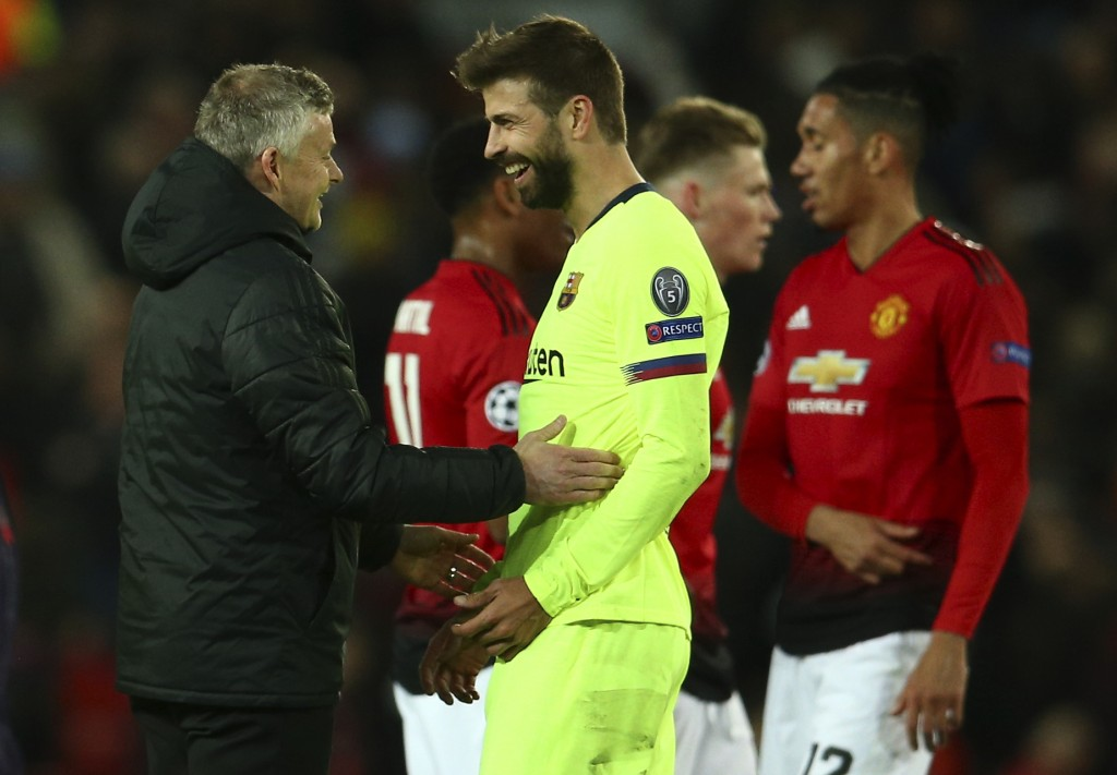 Manchester United coach Ole Gunnar Solskjaer, left, talks with Barcelona's Gerard Pique at the end of the Champions League quarterfinal, first leg, so