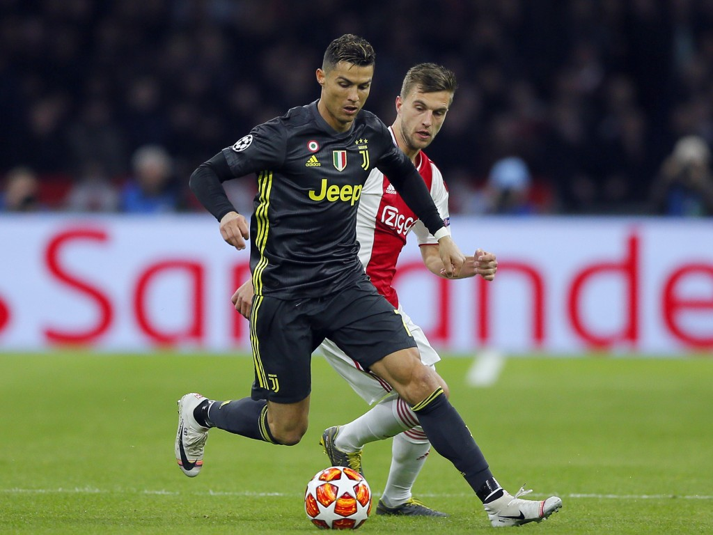FILE - In this Wednesday, April 10, 2019 file photo, Juventus forward Cristiano Ronaldo, front, duels for the ball with Ajax's Joel Veltman during the...