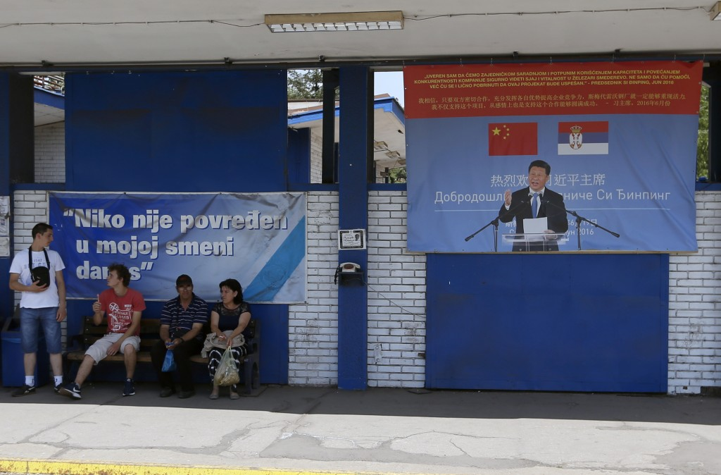 FILE - In this June 29, 2017, file photo, workers rest near billboard showing Chinese President Xi Jinping, reading: ''Welcome President'', right, and