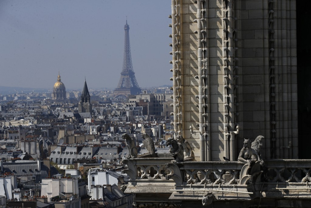 View from the top of the Paris' Notre Dame Cathedral with the Eiffel Tower in background as the religious statues descend to earth for the first time