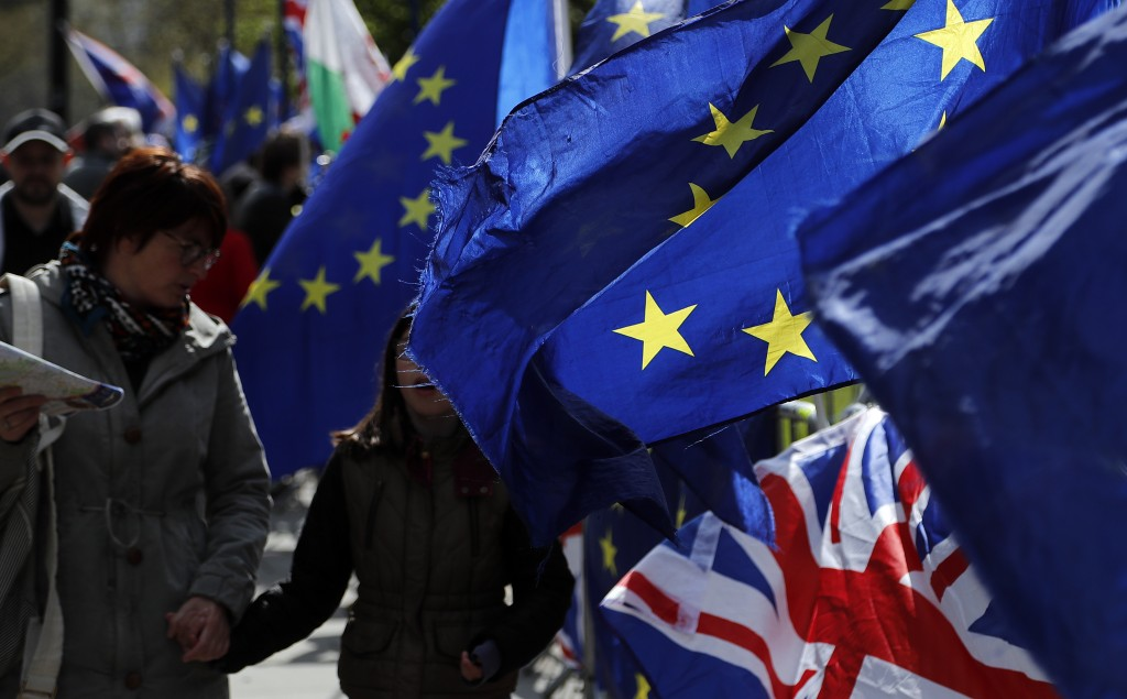 Protestor flags fly opposite the Houses of Parliament in London, Thursday, April 11, 2019. European Union leaders on Thursday offered Britain an exten...