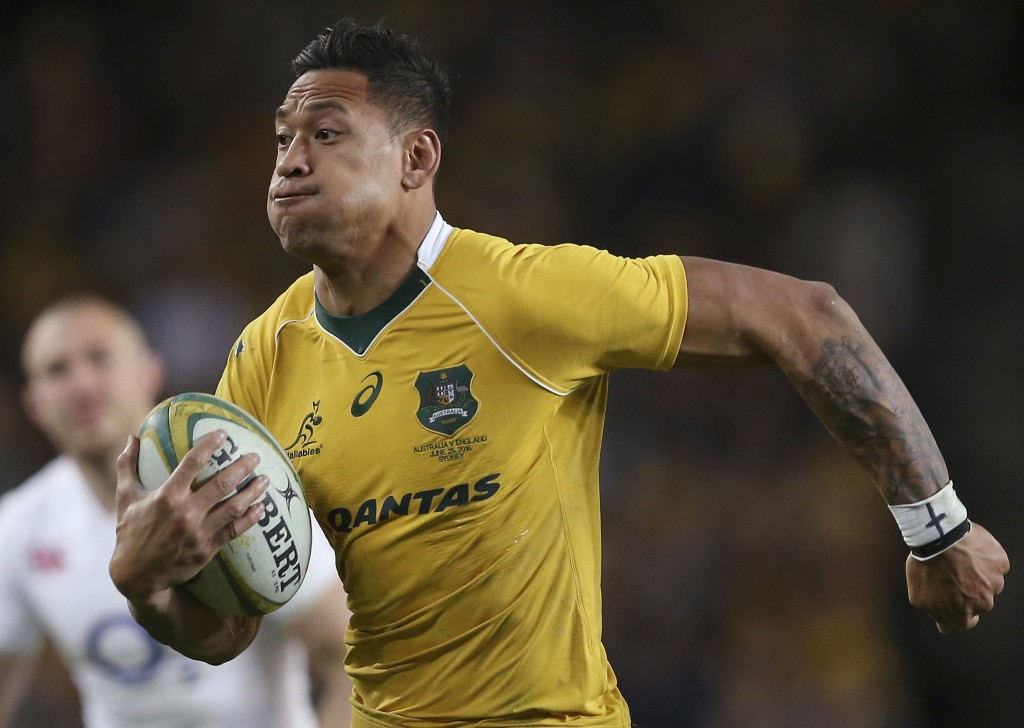 In this June 25, 2016, photo, Australian rugby union player Israel Folau, wearing tape on his wrist adorned with a cross, runs toward the try line to