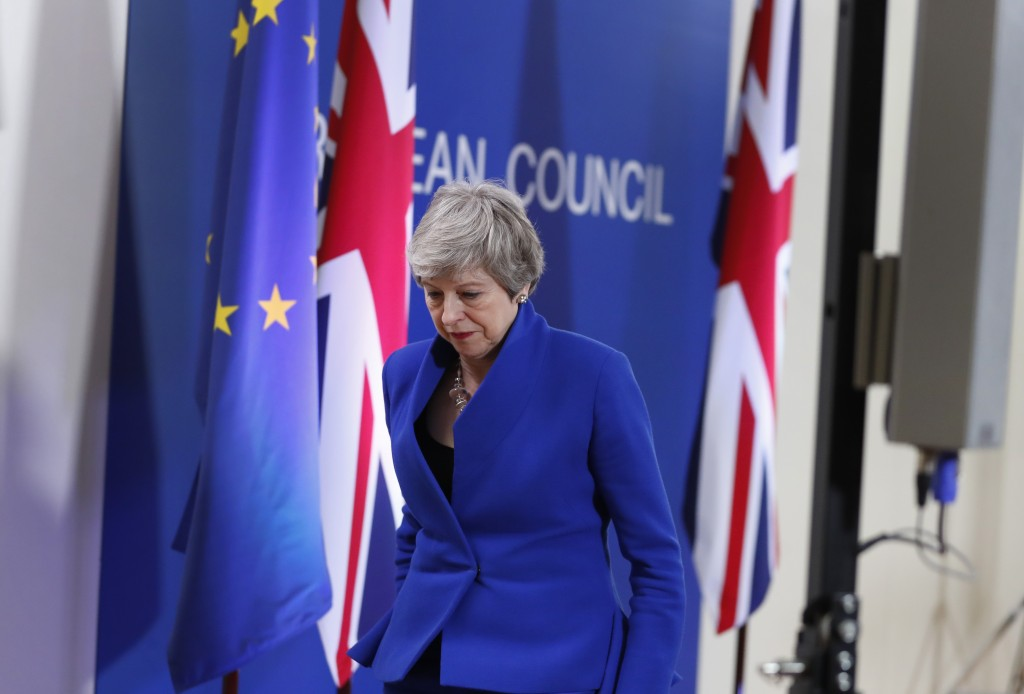 British Prime Minister Theresa May leaves the podium after addressing a media conference at the conclusion of an EU summit in Brussels, Thursday, Apri...