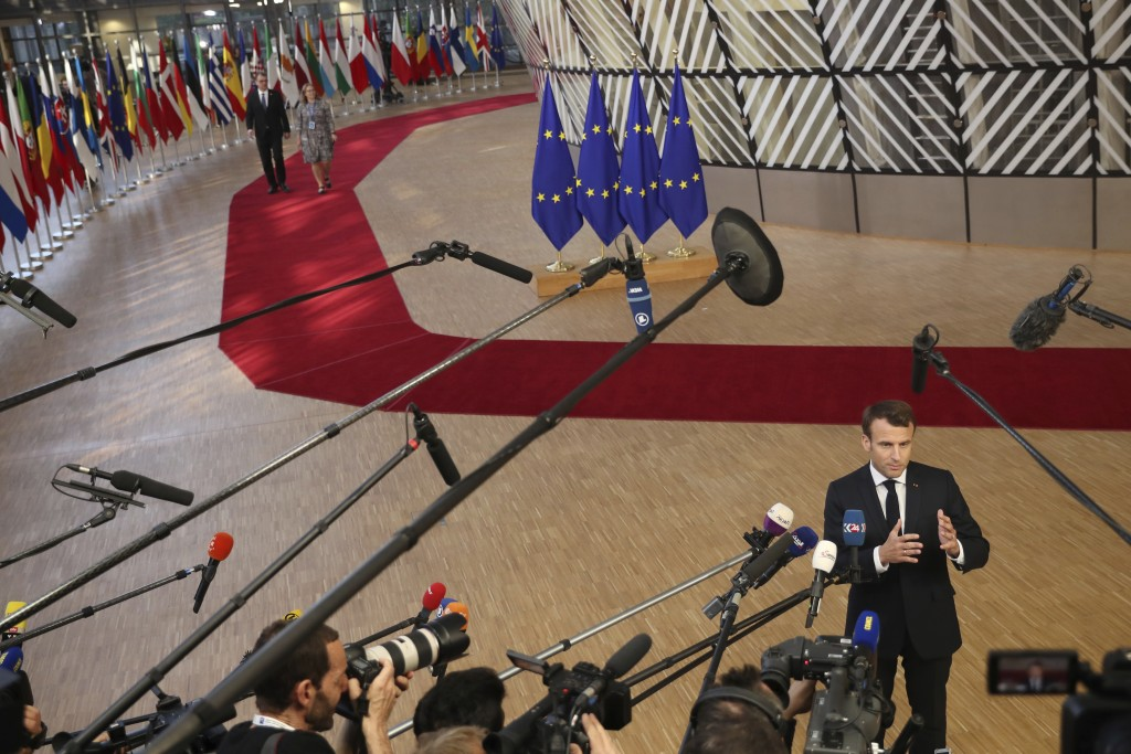 French President Emmanuel Macron speaks with the media as he arrives for an EU summit at the Europa building in Brussels, Wednesday, April 10, 2019. E...