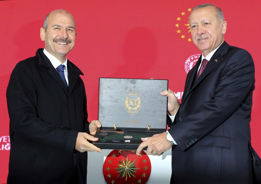 Turkey's President Recep Tayyip Erdogan, right, receives a souvenir from his Interior Minister Suleyman Soylu during a ceremony at the headquarters of