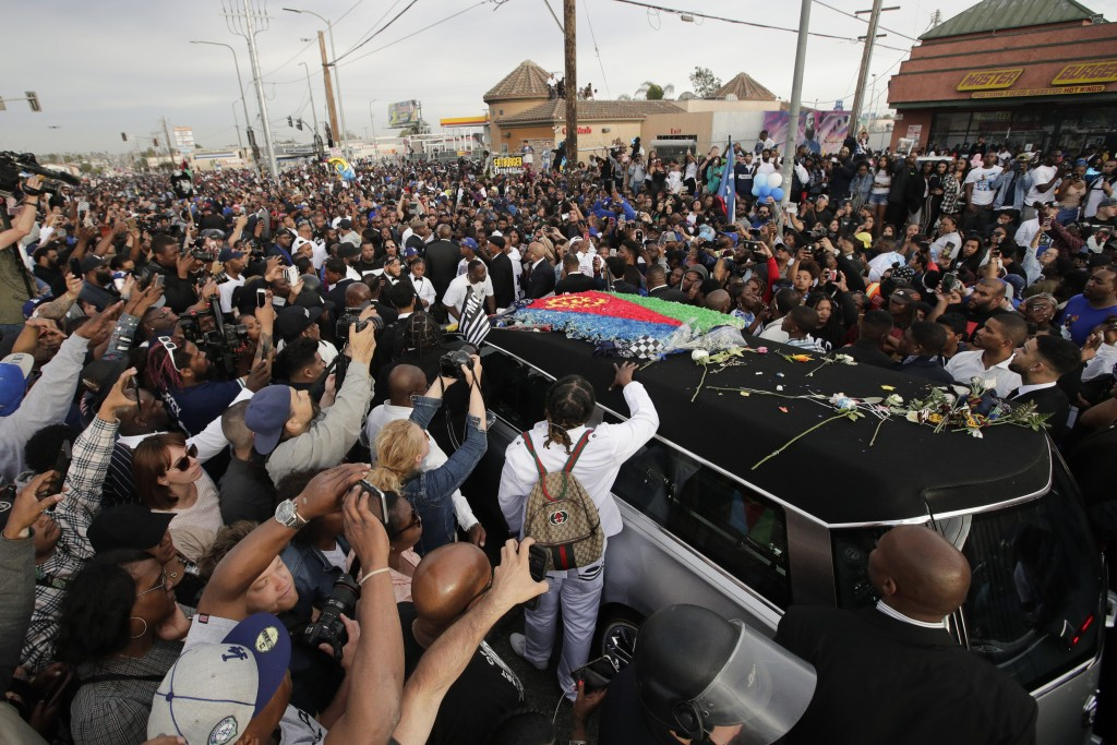 A hearse carrying the casket of slain rapper Nipsey Hussle, draped in the flag of his father's native country, Eritrea in East Africa, passes through