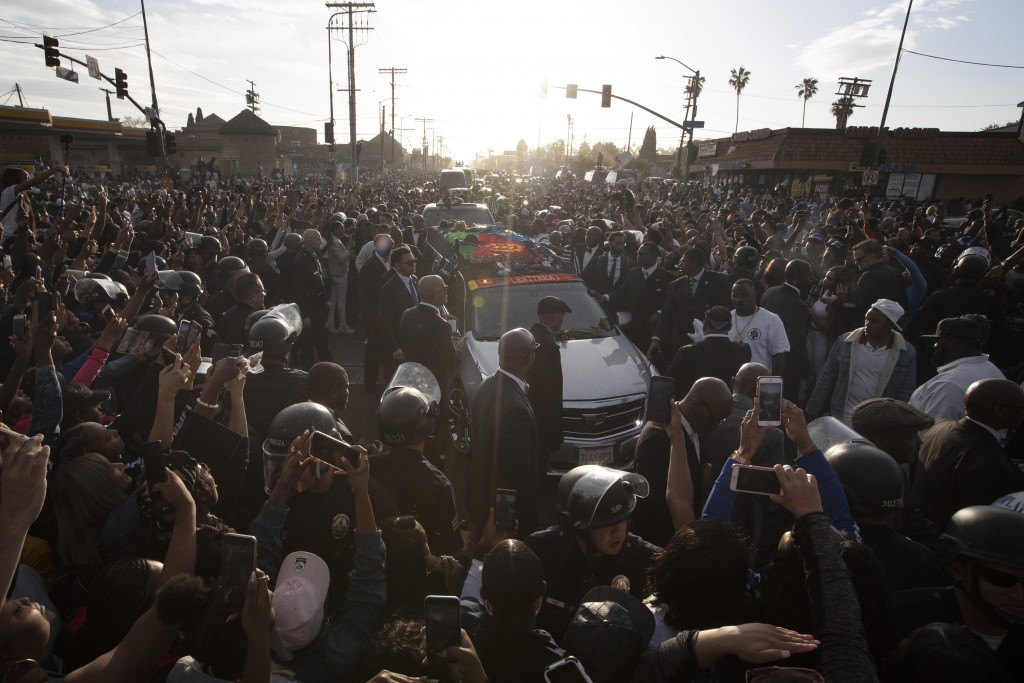 A hearse carrying the casket of slain rapper Nipsey Hussle passes through a large crowd on its 25-mile trek through the streets of the city Thursday,