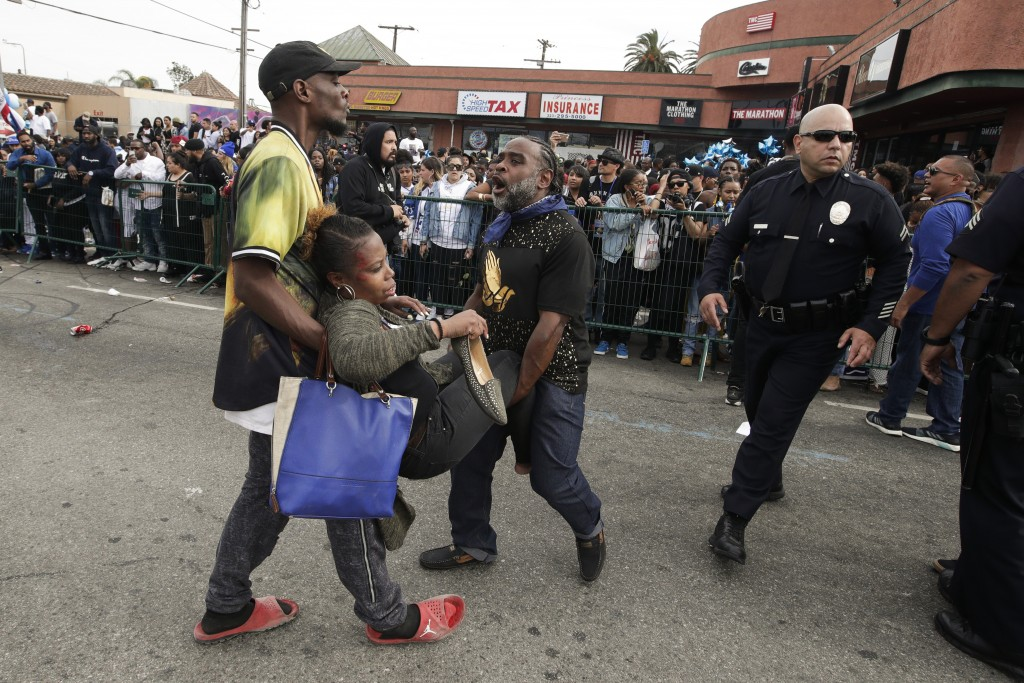 Two men carry a woman injured in a stampede as people gather to watch a hearse carrying the casket of slain rapper Nipsey Hussle Thursday, April 11, 2