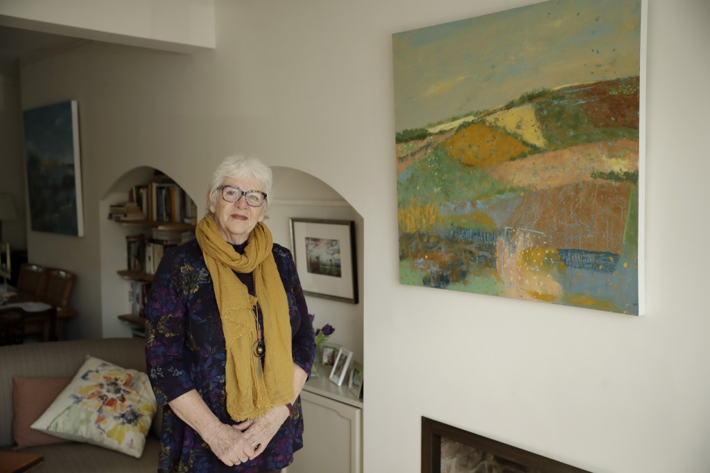 Elly Wright, a Dutch painter who has lived in Britain for 51-years, poses for photographs next to one of her paintings at her home in Epsom, on the so