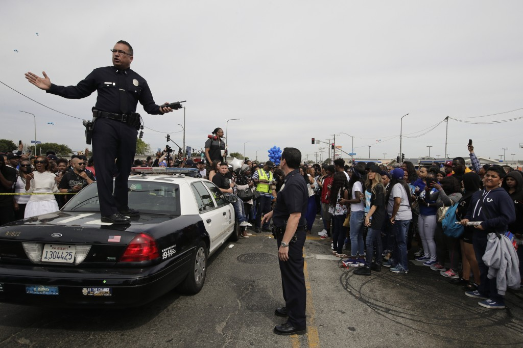 Los Angeles police officers tell the crowd to back up to clear the way for a hearse carrying the casket of slain rapper Nipsey Hussle Thursday, April