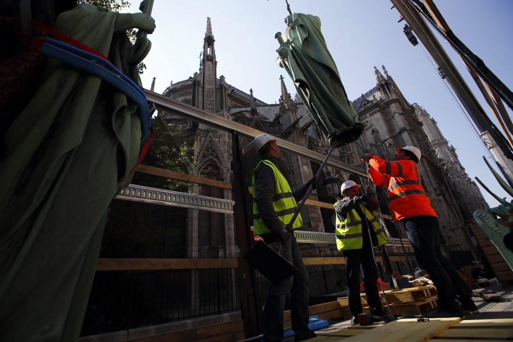 Workers secure a religious statue perched atop Paris' Notre Dame Cathedral as it descends to earth for the first time in over a century as part of a r